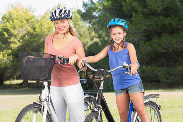 Portrait of daughter and mother with bikes