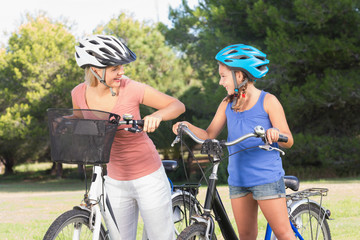Mother and daughter chatting and standing with bikes