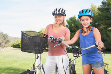 Portrait of mother and daughter with bicycles