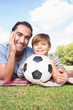 Portrait of father and son on picnic blanket with a football