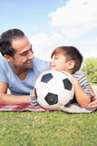 Happy father and son on picnic blanket with a football