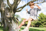 Cute boy on swing hanging from tree
