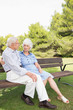 Elderly couple sitting on bench chatting