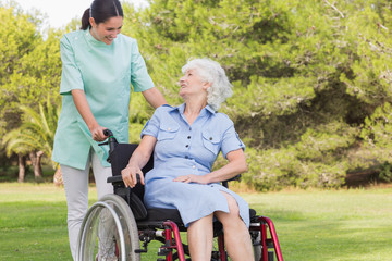 Nurse chatting with an old woman in wheelchair