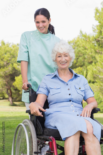 Portrait of nurse pushing elderly woman in wheelchair