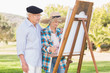Old couple wearing hats painting in the park