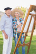 Portrait of elderly couple painting in the park