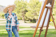 Old woman admiring her painting in the park