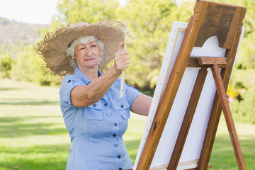 Old woman using easel to paint