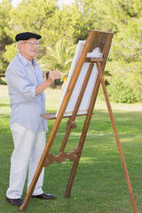 Old man painting outside using an easel
