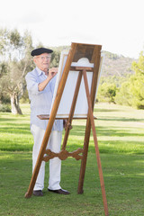 Old man painting a canvas in the park