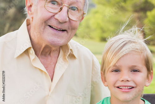 Portrait of grandfather and grandson in the park close up
