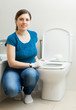 housewife cleaning toilet bowl with brush in bathroom