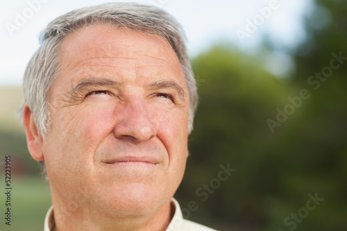 Thoughtful grey haired man looking into distance