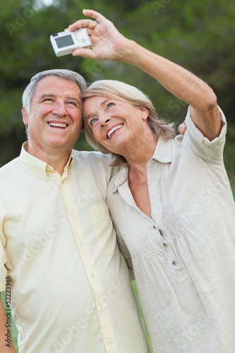 Older couple smiling for a photo they are taking themselves