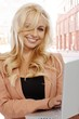 Blond businesswoman using laptop on street