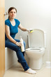 woman cleaning toilet bowl with sponge