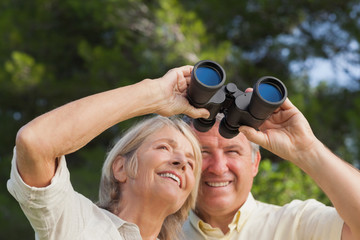 Happy older couple looking through binoculars