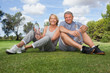 Portrait of older couple in sportswear with water bottles