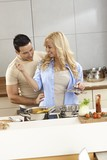 Loving couple cooking and tasting food in kitchen