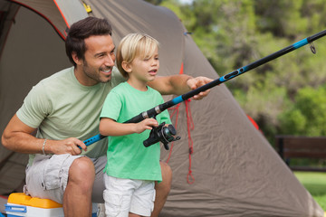 Father showing his son how to fish at camping site