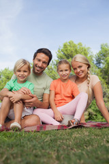 Portrait of happy family sitting on picnic blanket