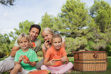 Happy family having a picnic and eating watermelon portrait