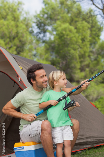 Father showing his son how to fish on camping holiday