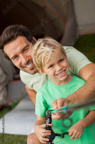 Portrait of father showing young son how to fish