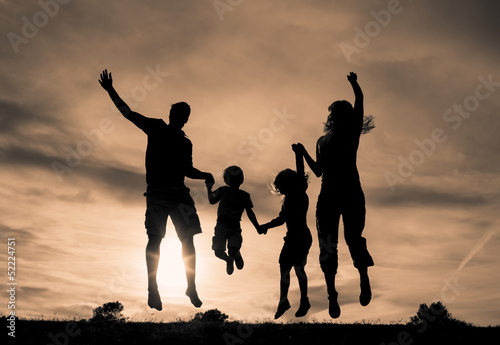 Family jumping together at sunset in the park