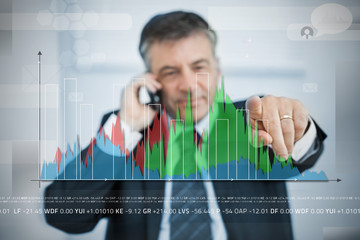 Businessman selecting point on large graph on touchscreen
