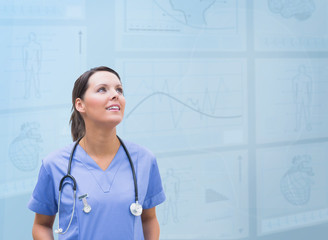 Nurse looking up against blue digital background