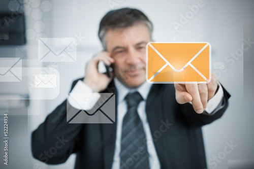Businessman selecting new mail symbol on touchscreen