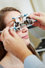 Optician putting trial glasses in trial frame