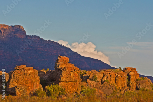 Rocks in evening light with mountain and cloud