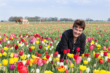 Portrait of a happy woman  in Dutch tulips field