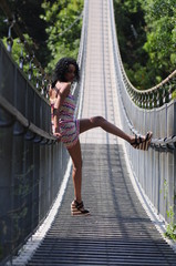 Pretty young woman on the suspension bridge
