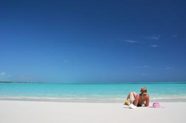 Girl with a glass of orange juice on the beach of Exuma, Bahamas