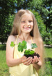 Little girl holding a seedling in cupped hands