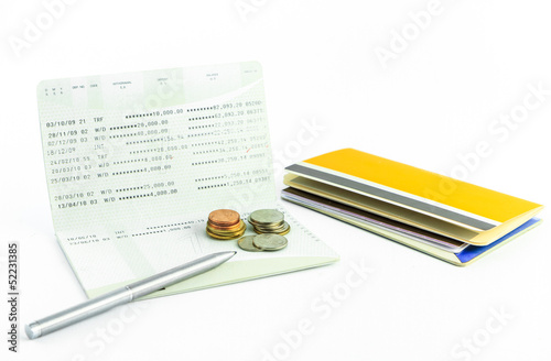 Coins and pen on account passbook isolate