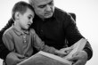 Portrait of a  man reading a story book for his grandson