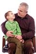 Portrait of a grandpa with his happy grandson sitting in armchai