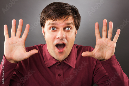 Young man with astonished expression and hands up