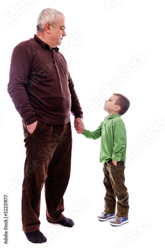 Senior man holding his grandson's hand, both with hand in pocket