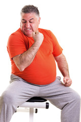 Overweight man showing his strength after doing exercises seted