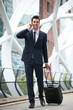 Confident businessman traveling with phone and bag