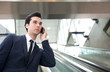 Traveling businessman talking on the phone on escalator