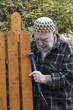 old man with kufi hat and tools repairing a gate