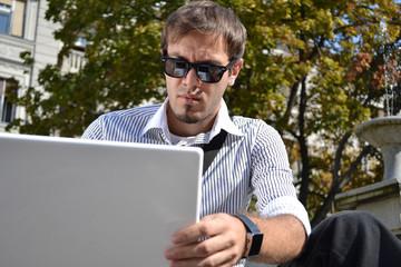 macho businessman using his notebook outdoor