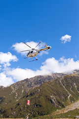 Transport helicopter fly over mountain wilderness